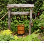 Traditional Wooden garden well with water Bucket hanging on a rope and hook